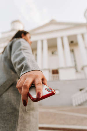 Girl with a red cell phone in hand in a cityscape. Phone close up