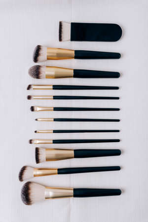 Set of makeup brushes on white fabric