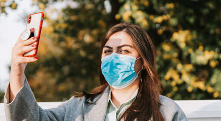 Portrait of a beautiful adult young woman on the background of autumn in the Park in a medical face mask with a phone in her hands Standard-Bild