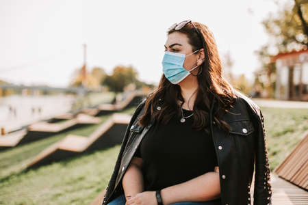 Large portrait of a beautiful woman in a medical mask and leather jacket in a Park in nature