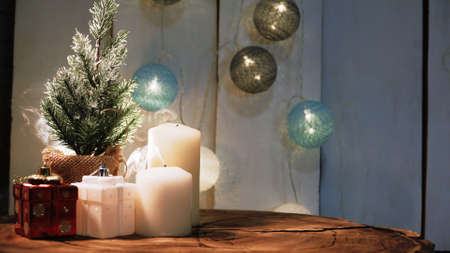 Small Christmas tree and candles on a wooden background