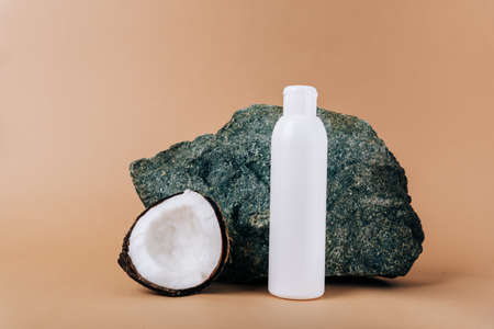 Coconut and a tube of cosmetics on a stone background Standard-Bild
