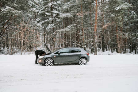 A car with an open hood on the background of a winter forest