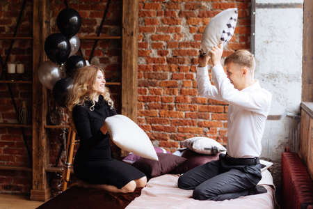 A young man and a woman fight with pillows on a bed in a loft-style room Reklamní fotografie