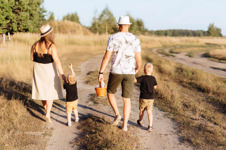 A young family with two children walks in nature outside the city in the summer Reklamní fotografie