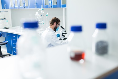 Biological laboratory. Professional smart nice scientist sitting in the laboratory and studying test samples while being at work