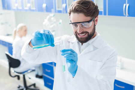 Enthusiastic scientist. Happy positive delighted man wearing protective glasses and smiling while working with chemical reagents