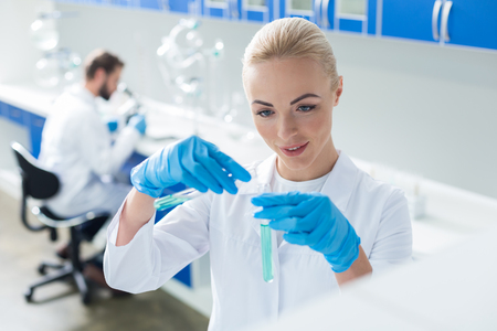 Chemical analysis. Nice cheerful blonde woman holding test tubes and doing chemical analysis of the liquid while working in the lab Stock Photo