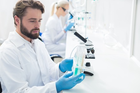 Scientific modifications. Smart pleasant hard working scientist sitting in the lab and holding a rack with test tubes while studying them Stock Photo