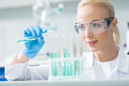 Modern chemistry. Cheerful nice female chemist wearing protective glasses and looking at the test tubes while doing an experiment