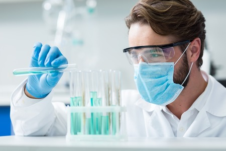Professional chemist. Smart nice male researcher wearing a mask and protective glasses while conducting chemical experiment in the lab Stock Photo