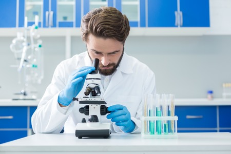 Biological research. Smart nice confident scientist looking into the microscope and testing the samples while doing the biological research Stock Photo