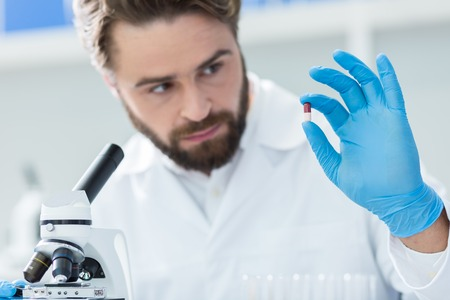 New medicine. Serious nice smart scientist holding a pill and looking at it while developing new medicine Stock Photo