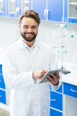 Technological gadget. Delighted nice handsome man holding a tablet and smiling while working in the biological lab Stock Photo