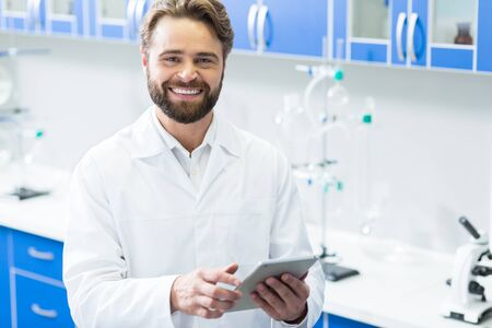 Positive mood. Delighted handsome nice biologist smiling and looking at you while holding a tab let in his hand