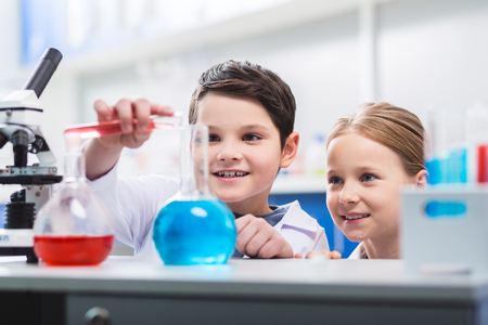 Reckless behavior. Joyful jolly merry kids staring at laboratory glasses while smiling and conducting experiment Stock Photo