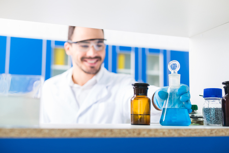 Lab inside. Selective focus of male hand taking lab glasses with liquids poured in and standing on surface