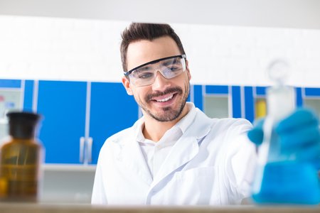 male laboratorian wearing safety glasses while smiling and looking at bulb