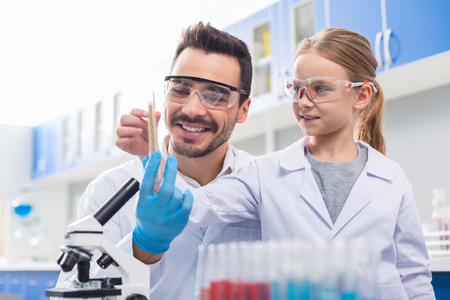 Smart child. Positive joyful nice girl smiling and looking at the test tube while studying science Stock Photo
