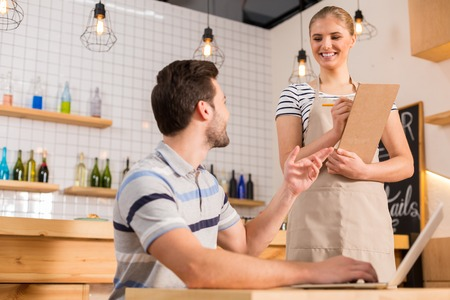 I want food. Joyful nice hungry man looking at the waitress and making an order while being in the cafe