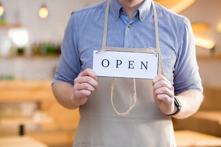 Opening sign. Close up of a label tag with an inscription open being in hands of a nice handsome cafe worker Stock Photo