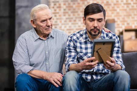 Dont be upset. Moody man holding a photo frame while his retired father supporting him