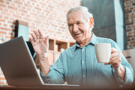 Video call. Nice positive aged man holding a cup of tea and showing a greeting gesture while making a video call Stock fotó