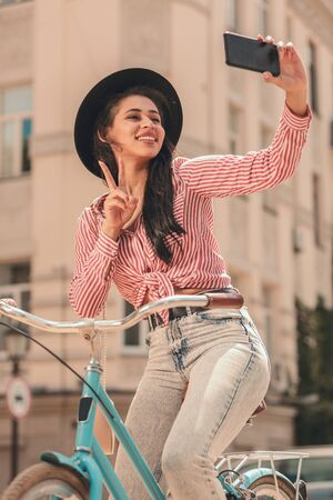 Pretty woman posing for selfie on the bike stock photo Фото со стока