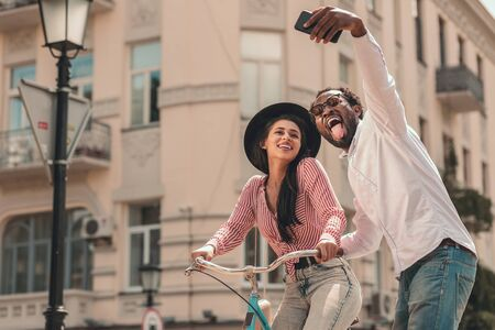 Man taking selfie with woman on the bike stock photo