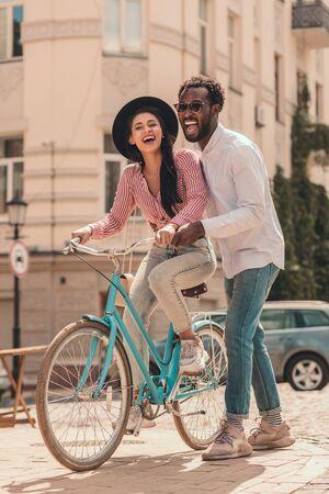 Happy man helping girlfriend with bike stock photo Фото со стока