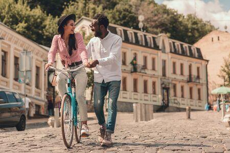 Glad couple enjoying walk and riding bike stock photo