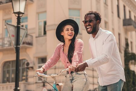 Excited man helping woman to ride her bike stock photo