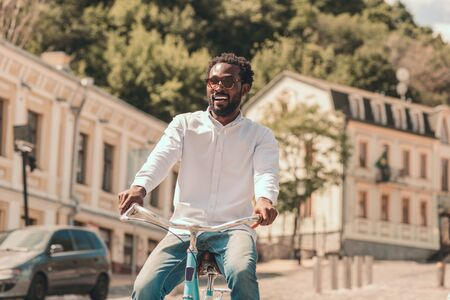 Happy man riding bicycle outdoors stock photo