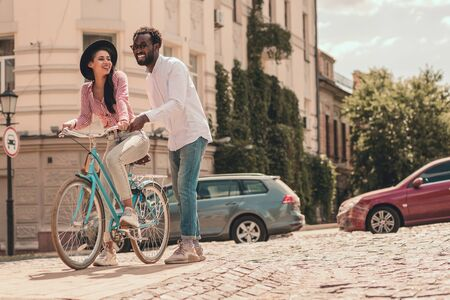 Woman sitting on the bike and man smiling stock photo