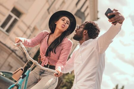 Lady on the bike taking selfie with boyfriend stock photo