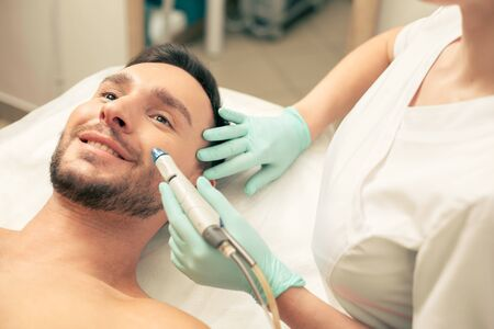 Man smiling and cosmetologist treating his face skin Foto de archivo