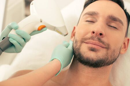 Peaceful man smiling and relaxing at the laser procedure