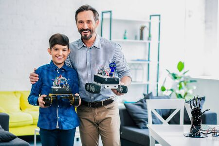 Positive father and his smart son holding their robots