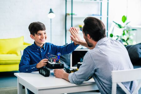 Joyful smart boy giving high five to his father