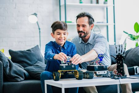 Overjoyed father helping his son with robot constructing