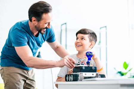 Positive nice father helping his son with engineering