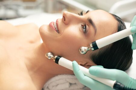 Close up of smiling lady during the microcurrent therapy