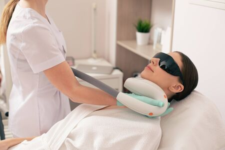 Cosmetologist using special device for laser hair removal on the neck