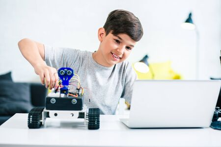 Joyful little boy constructing modern robot at home Stockfoto