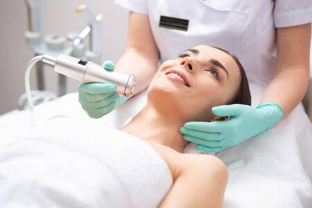 Vrolijke jonge dame liggend op de medische bank en professionele schoonheidsspecialiste die zuurstof meso-therapie uitvoert