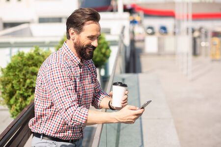 Joyful handsoem man using his smartphone outdoors