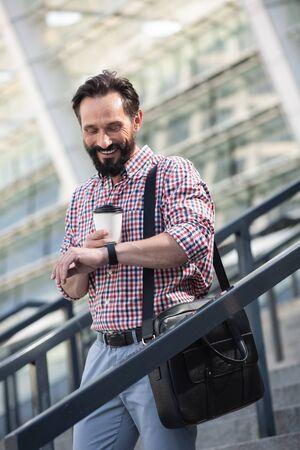 Joyful adult man using his wristwatch outdoors Zdjęcie Seryjne