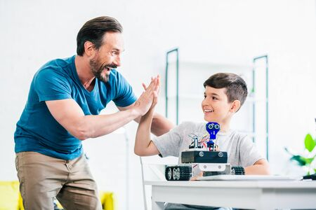 Happy father and son completing their engineering project
