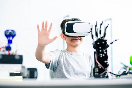 Cheerful ingenious little boy wearing VR device while experimenting with his robotic creating at home