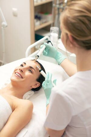 Careful cosmetologist using prongs during the procedure